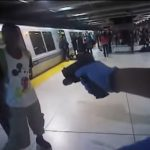 A BART police officer holds Michael Smith at gunpoint during an arrest at the Embarcadero station. Body camera still.