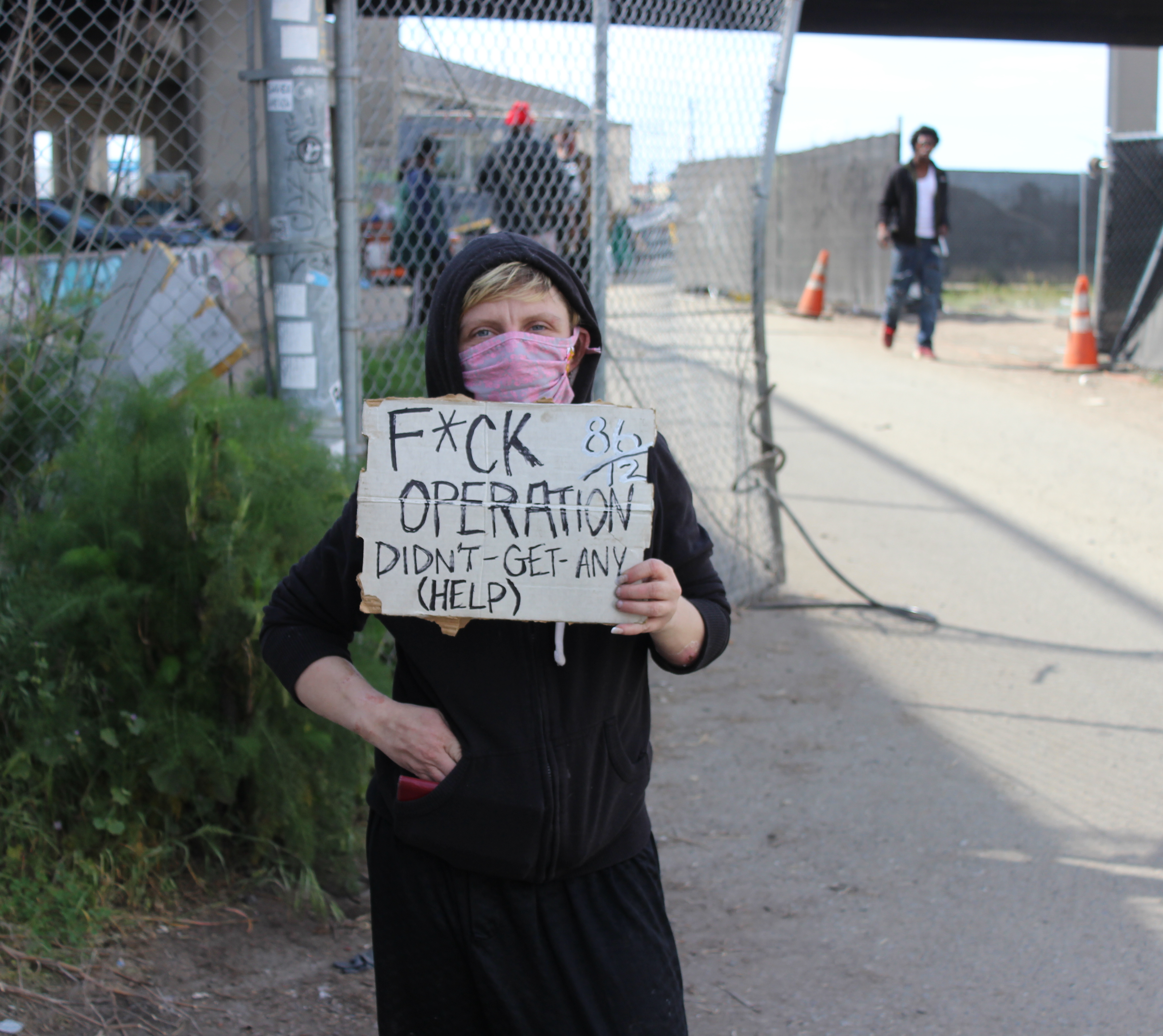 Jessica Bailey, who is unhoused, poses at Wood St, where she currently lives, with a sign she brought to the protest outside of Mayor Libby Schaaf's home on Monday. Her sign criticizes Operation Dignity, the non-profit who has contracted with the city of Oakland to run the Tuff Shed site that Baily lived in for over three months. Photo by Zack Haber.